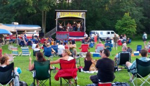 A picture of the stage at The Commons with folks on the lawn in chairs enjoying the Summer Concert Series in High Bridge, NJ.